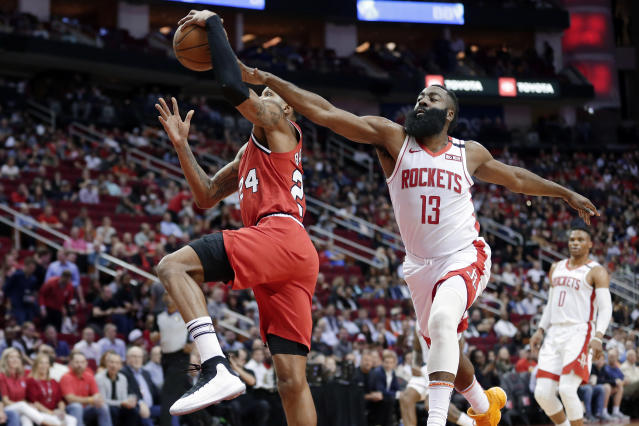 Portland Trail Blazers guard Kent Bazemore (24) is fouled on his shot attempt by Houston Rockets guard James Harden (13) during the first half of an NBA basketball game Wednesday, Jan. 15, 2020, in Houston. (AP Photo/Michael Wyke)
