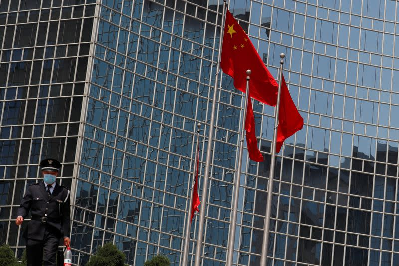 A security guard walks near the Chinese national flag in Beijing