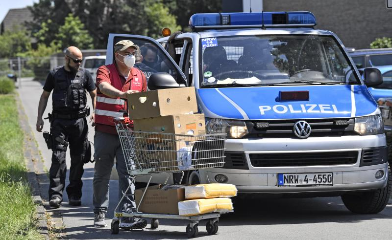 Helpers bring food to families behind a fence, who are quarantined in their apartments in Verl, Germany, Tuesday, June 23, 2020. Following the corona outbreak at meat processor Toennies in Rheda-Wiedenbrueck, the federal state authorities are massively restricting public life in the Guetersloh district with a lockdown. (AP Photo/Martin Meissner)
