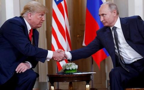 US President Donald Trump, left, and Russian President Vladimir Putin, right, shake hands at the beginning of a meeting at the Presidential Palace in Helsinki, Finland - Credit: Pablo Martinez Monsivais/AP