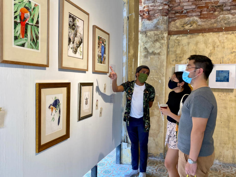 Curator Ivan Gabriel (left) explaining about the artwork to visitors during the exhibition.