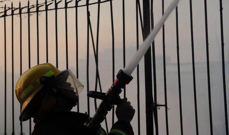 A firefighter extinguishes a fire in Quezon City, east of the Philippine capital of Manila on April 19, 2012. Three American men and a South Korean were among seven people who died on Friday when a fire razed a hotel in a red-light district near a former US naval base in the Philippines, authorities said