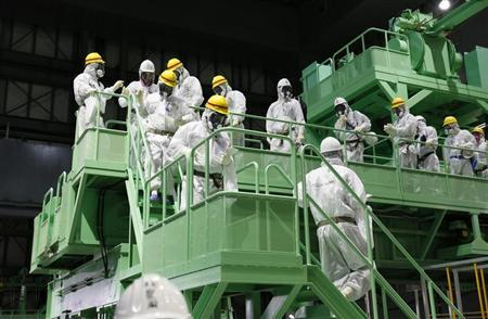 Members of the media and TEPCO employees walk down the steps of a fuel handling machine inside the No.4 reactor building in Fukushima