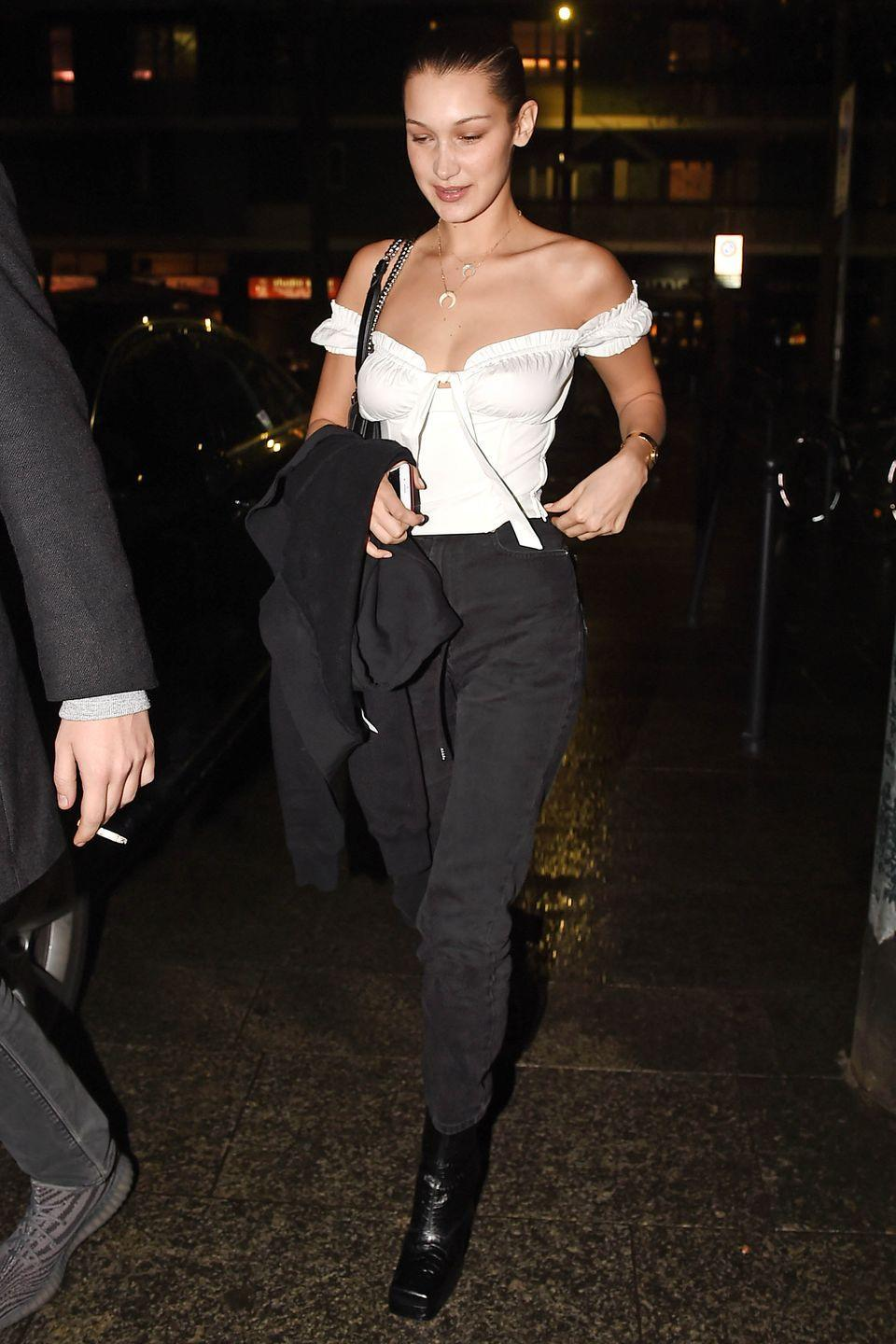 <p>In a white an I.Am.Gia off-the-shoulder shirt, black pants, and square toe boots while out in Milan.</p>