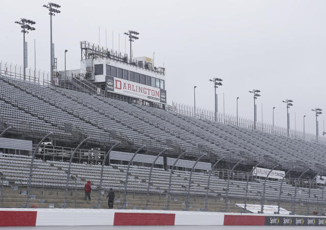 FILE - In this Sept. 2, 2016, file photo, workers walk along the grandstands in the rain at Darlington Raceway after weather forced NASCAR to call off qualifying for the Sprint Cup and XFinity series auto races. NASCAR says it will resume its season without fans present starting May 17 at Darlington Raceway in South Carolina. (AP Photo/Terry Renna, File)