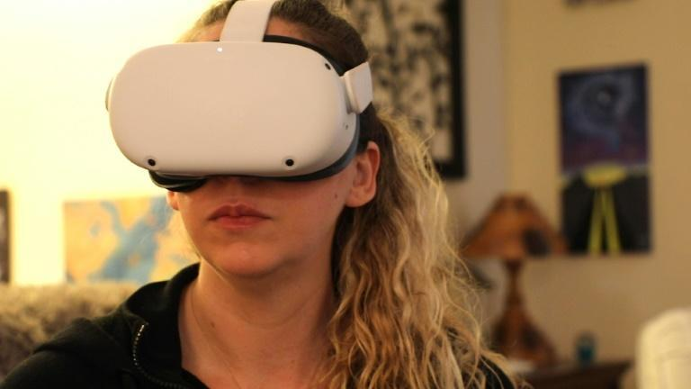 Amy Erdt, seen with Oculus headset, on March 19, says virtual reality can help people experience travel and new destinations even if they are in a pendemic lockdown