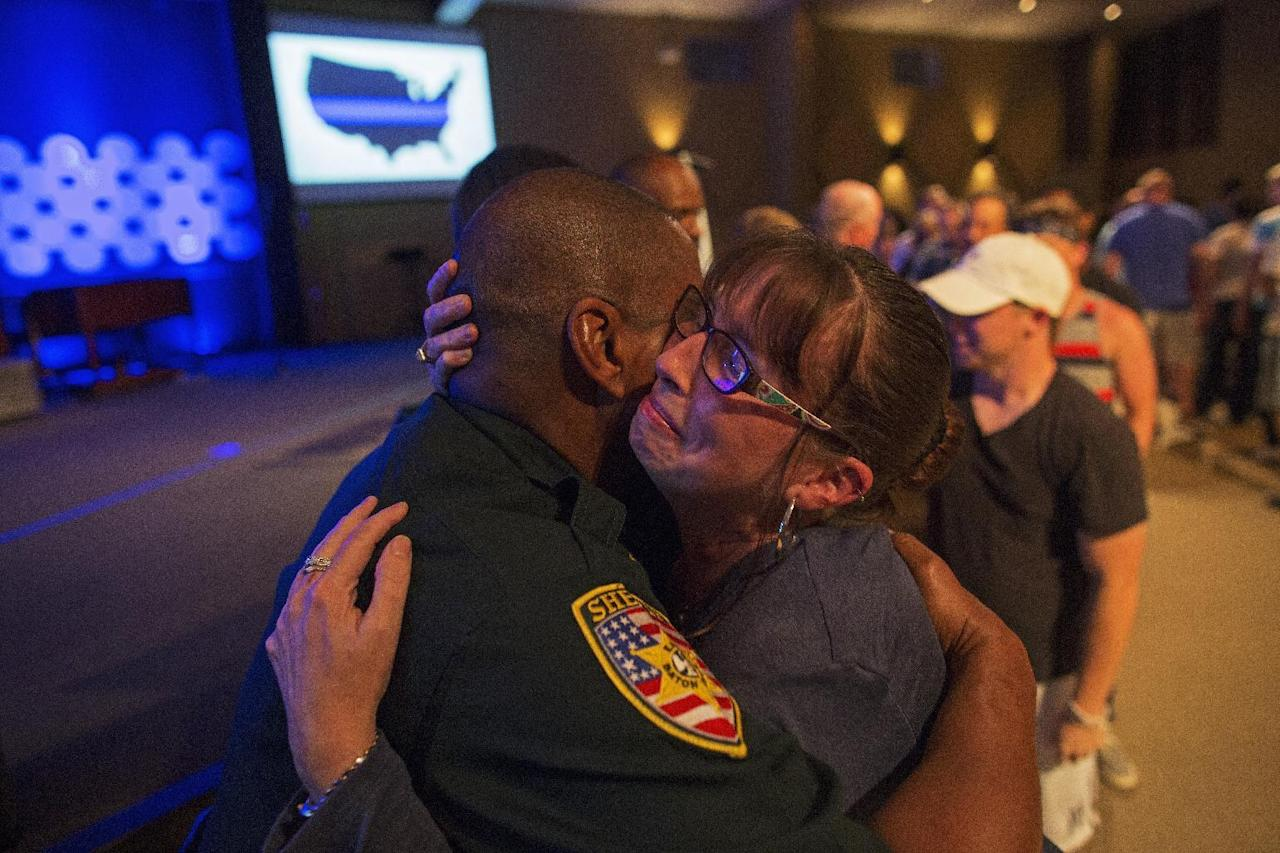 East Baton Rouge Sheriff officer Eddie Guidry is hugged by a teary Terri Carney, both members of The Rock Church which is a ministry on the outskirts of Baton Rouge, during a prayer vigil for the officers killed and wounded by a gunman on Sunday as well as members of the local law enforcement community in Zachary, La., Monday, July 18, 2016. About 100 people came to the special hour long prayer vigil. (AP Photo/Max Becherer)