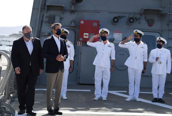 US Secretary of State Mike Pompeo, left, arrives with the Greek Prime Minister Kyriakos Mitsotakis on the Greek frigate Salamis during their visit to the Naval Support Activity base at Souda, the foremost US naval facility in the eastern Mediterranean, on the Greek island of Crete, Tuesday, Sept. 29, 2020. Pompeo visited a U.S. naval base at Souda Bay on the southern Greek island of Crete Tuesday, ahead of a meeting with Greece's prime minister on the second day of his trip to the country. (Aris Messinis/Pool viaAP)