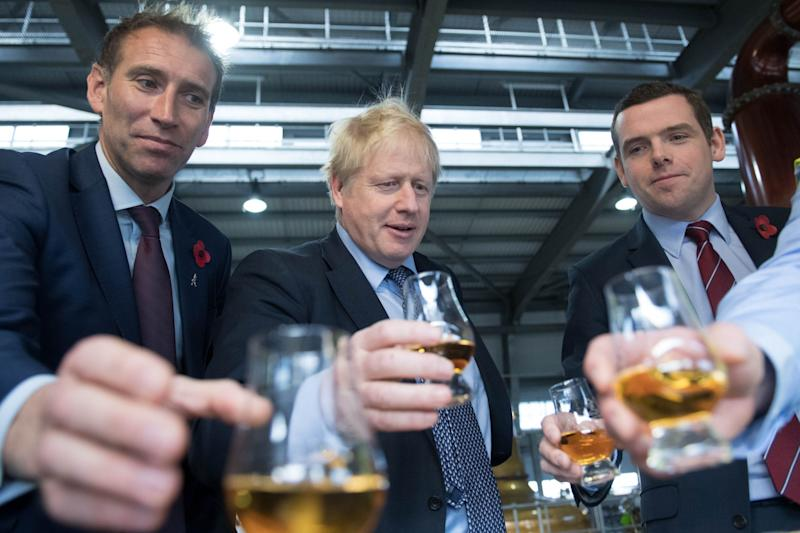 Prime Minister Boris Johnson tastes whisky at the Roseisle Distillery (PA)