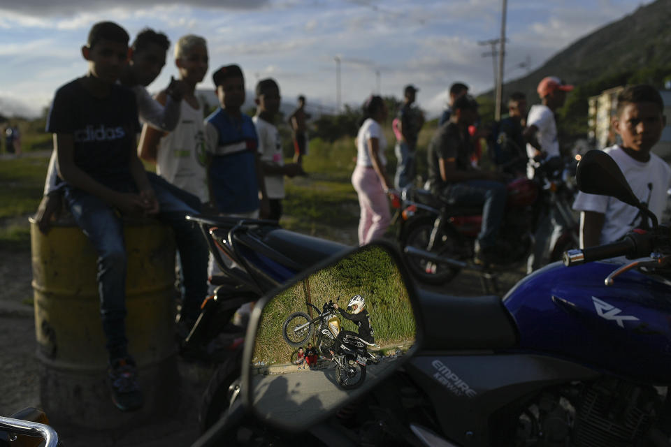"""Reflected in a motorcycle side mirror, stuntman Pedro Aldana performs a wheelie on his motorbike during an exhibition in the Ojo de Agua neighborhood of Caracas, Venezuela, Sunday, Jan. 10, 2021. """"This is my passion and my work,"""" he said. (AP Photo/Matias Delacroix)"""