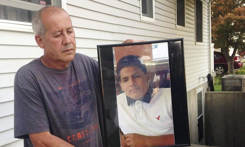 Abraham Chaparro with a photograph of his murdered stepson, Miguel Garcia-Moran, outside his home in Brentwood.