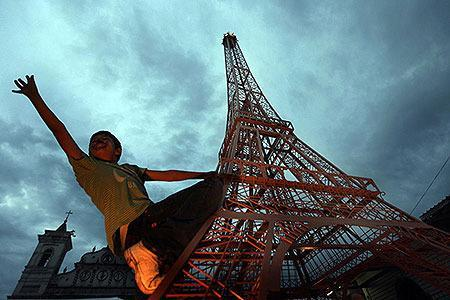 HONDURAS: A boy plays on a replica of the Eiffel Tower at Los Dolores square in Tegucigalpa July 18, 2010. The French embassy in Honduras donated the 6 metre (20 feet) replica to the city of Tegucigalpa to commemorate France's 221 years of independence on Sunday. The replica was the first in Latin America and the 18th in the world, according to embassy officials.