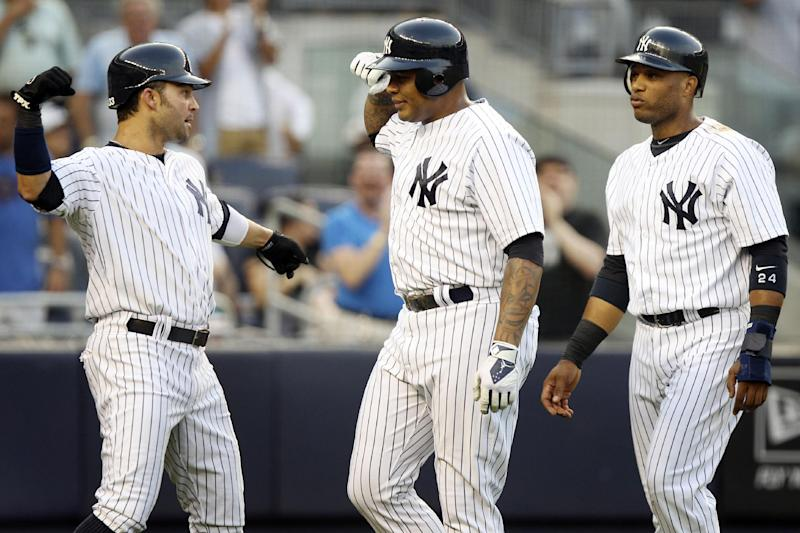 New York Yankees' Andruw Jones, center, is greeted by Robinson Cano, right, and Nick Swisher after they scored on a three-run home run hit by Jones during the second inning of a baseball game against the Toronto Blue Jays, Tuesday, July 17, 2012, at Yankee Stadium in New York. (AP Photo/Seth Wenig)