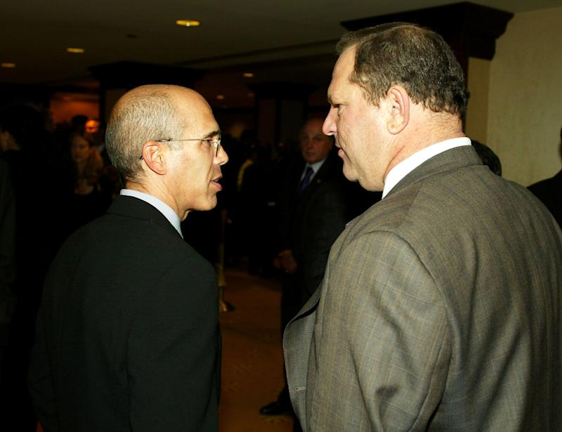 Jeffrey Katzenberg and Harvey Weinstein talk at a charity dinner on Sept. 25, 2003.