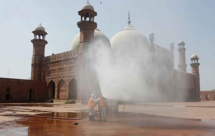 Volunteers disinfects the historical Badshahi Mosque ahead of the Muslim fasting month of Ramadan, in Lahore, Pakistan, Wednesday, April 22, 2020. (AP Photo/K.M. Chaudhry)