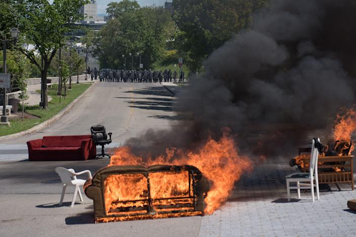 <p>Furniture set on fire by protesters burns during a demonstration in Quebec City on June 8, 2018, as the G7 Summits gets underway. (Photo: Alice Chiche/AFP/Getty Images) </p>