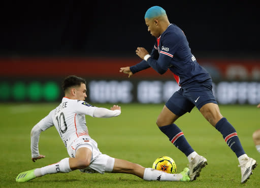 PSG's Kylian Mbappe, right, challenges with Lorient's Enzo Le Fee, during the French League One soccer match between Paris Saint-Germain and Lorient at the Parc des Princes in Paris, France, Wednesday, Dec. 16, 2020. (AP Photo/Christophe Ena)