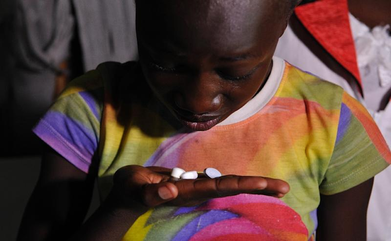Claudia Aulo, a 13-year-old Kenyan girl living with AIDS and who lost both parents to the disease, takes her drugs at grandmother's house in Ndiwa (AFP Photo/Simon Maina)