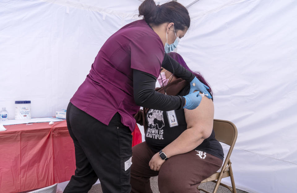 Joana Luna, a temporary medical assistant, left, inoculates Carmen Jimenez, 35, a resident of ZIP code 90001, at the St. John's Well Child and Family Center's COVID-19 vaccination site at the East Los Angeles Civic Center in Los Angeles, Thursday, March 4, 2021. California will begin setting aside 40% of all vaccine doses for the state's most vulnerable neighborhoods in an effort to inoculate people most at risk from the coronavirus more quickly. (AP Photo/Damian Dovarganes)