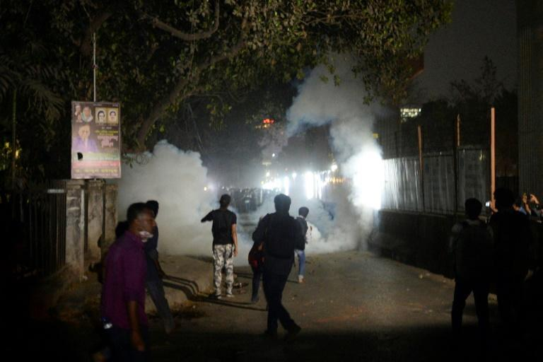 Protesters threw bricks amid teargas smoke fired by the police during clashes at Dhaka University on Friday