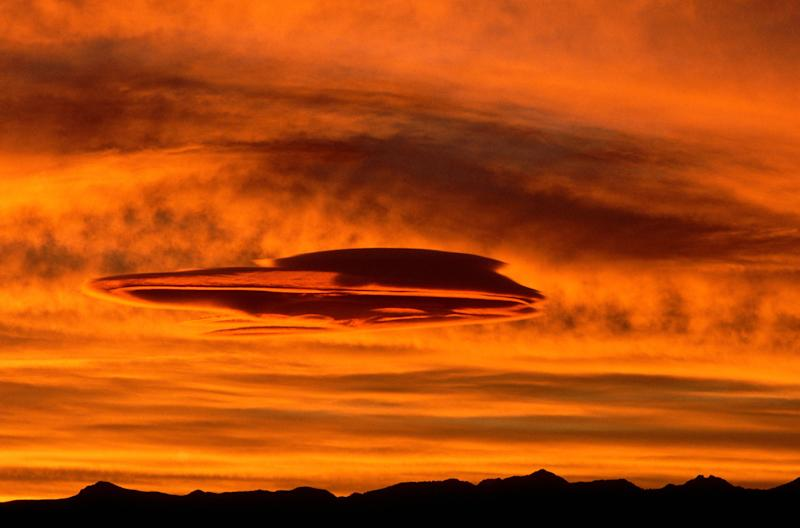 Lenticular clouds form a saucer shape in the orange glow of the sunset. Sumner Valley, Washington, USA.