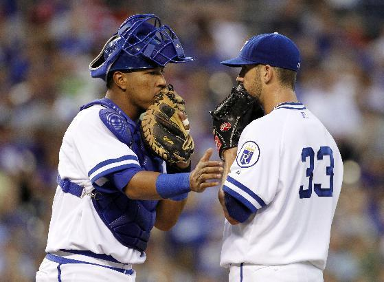 Kansas City Royals catcher Salvador Perez, left, talks with pitcher James Shields, right, after a run was scored by the Cleveland Indians in the fourth inning of a baseball game in Kansas City, Mo., Saturday, Aug. 30, 2014. (AP Photo/Colin E. Braley)