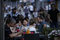 People relax after a hot day at an outdoor terrace of a restaurant in Moscow, Russia, Wednesday, July 14, 2021. The Russian capital recorded new record temperatures amid a heat wave this month with today's temperatures forecast 33 degrees Celsius (91,4 Fahrenheit). (AP Photo/Alexander Zemlianichenko)