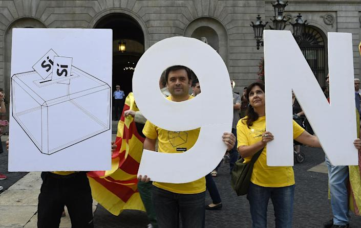 """Pro-independence Catalans hold placards representing a ballot box and the date of the vote """"9N"""" on Sant Jaume Square in Barcelona, September 27, 2014 (AFP Photo/Lluis Gene)"""