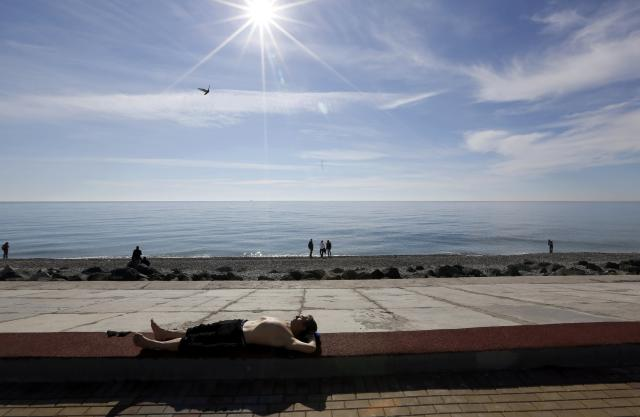 A man sun-bathes along the Black Sea near the Olympic Park during the 2014 Sochi Winter Olympics, February 12, 2014 . REUTERS/Reinhard Krause (RUSSIA - Tags: SPORT OLYMPICS ENVIRONMENT TPX IMAGES OF THE DAY)