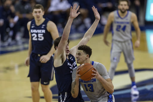 Creighton forward Christian Bishop (13) drives to the basket against Xavier forward Zach Freemantle (32) for a lay up in the second half during an NCAA college basketball game on Wednesday, Dec. 23, 2020, in Omaha, Neb. (AP Photo/John Peterson)