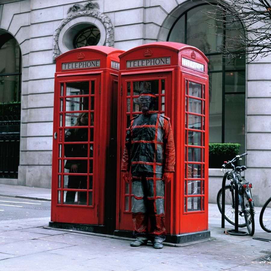 Liu Bolin camouflages himself against an iconic red London telephone box.