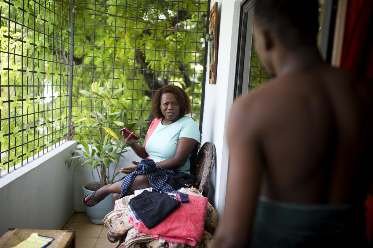 Yaisah Val, 46, a transgender woman, talks with her husband, Richecarde, 28, at their home in Port-au-Prince, Haiti, on July 12, 2018. She and her husband are seeking to raise funds to open a first-of-its-kind shelter for transgender Haitians that would help them pursue an education and get appropriate health care. (AP Photo/Dieu Nalio Chery)