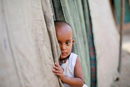 A girl from the Rohingya community stands outside her family's shack in a camp in New Delhi, October 4, 2018. REUTERS/Adnan Abidi/Files