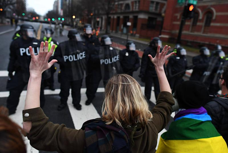 An anti-Trump protester holds her hands up as police officers lineup in Washington, DC,: JEWEL SAMAD/AFP/Getty Images