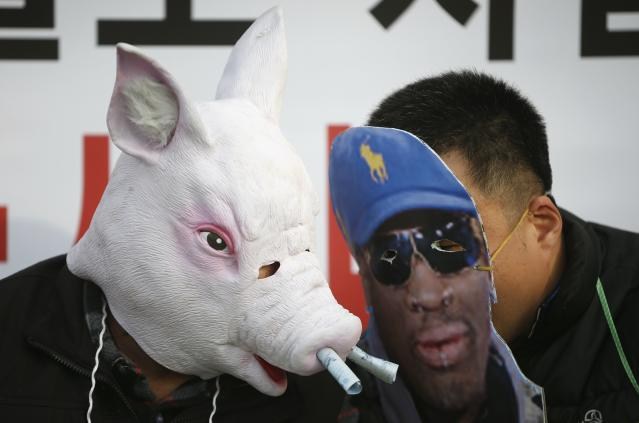 Protesters wearing masks attend a rally denouncing Rodman's visit to North Korea and North Korean leader Kim on Kim's birthday in central Seoul