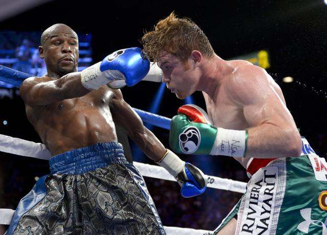 Canelo Alvarez, right, throws a jab at Floyd Mayweather Jr. in the fifth round during a 152-pound title fight, Saturday, Sept. 14, 2013, in Las Vegas. (AP Photo/Mark J. Terrill)