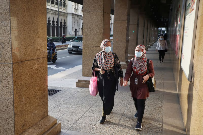 People wearing protective masks walk on a street, amid the coronavirus disease (COVID-19) outbreak in Kuala Lumpur