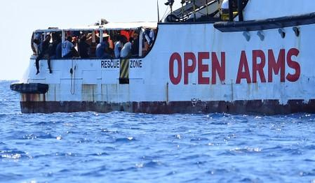 Migrants are seen aboard Spanish migrant rescue ship Open Arms, close to the Italian shore in Lampedusa