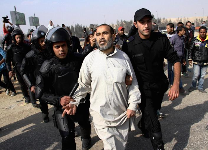 FILE - In this Wednesday, Jan. 8, 2014 file photo, Egypt's riot police officers arrest a man, center, following clashes between supporters of Egypt's ousted President Mohammed Morsi and riot police in Cairo, Egypt. Egypt's crackdown on Islamists has jailed 16,000 people over the past eight months in the country's biggest round-up in nearly two decades, according to previously unreleased figures from security officials. Rights activists say reports of abuses in prisons are mounting, with prisoners describing systematic beatings and miserable conditions for dozens packed into tiny cells. (AP Photo/Ahmed Gomaa, File)