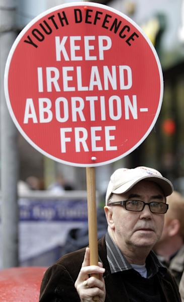 A protester opposed to abortion holds a placard outside the Marie Stopes clinic in Belfast, Northern Ireland, Thursday, 18, 2012. The first abortion clinic on the island of Ireland has opened in Belfast, sparking protests by Christian conservatives from both the Catholic and Protestant sides of Northern Ireland's divide. The Marie Stopes center plans to offer the abortion pill to women less than nine weeks pregnant _ but only if doctors determine they're at risk of death or long-term health damage from their pregnancy. That's the law in both Northern Ireland and the Republic of Ireland, where abortion is otherwise illegal. (AP Photo/Peter Morrison)