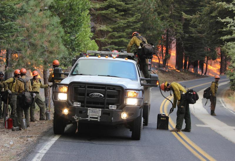 In this photo provided by the U.S. Forest Service, members of the Roosevelt Interagency Hotshot crew, from Fort Collins, Colo., gear up for a controlled burn operation as they fight the Rim Fire near Yosemite National Park in California Sunday, Sept. 1, 2013. The massive wildfire is now 75 percent contained according to a state fire spokesman. (AP Photo/U.S. Forest Service, Mike McMillan)