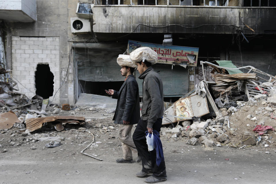 FILE - In this Jan. 20, 2017 file photo, Syrian men carry bags of bread on their heads while walking back to their homes in the once rebel-held Bustan al-Qasr neighborhood in the eastern Aleppo, Syria. As Syria marks the 10th anniversary Monday, March 15, 2021, of the start of its uprising-turned-civil war, President Bashar Assad may still be in power, propped up by Russia and Iran. But millions of people are being pushed deeper into poverty, and a majority of households can hardly scrape together enough to secure their next meal. (AP Photo/Hassan Ammar, File)