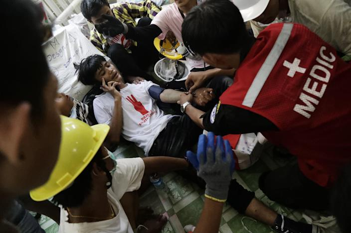 <p>Medics tend to an injured demonstrator during a protest against the military coup in Yangon, Myanmar, on 3 March 2021</p> (EPA)