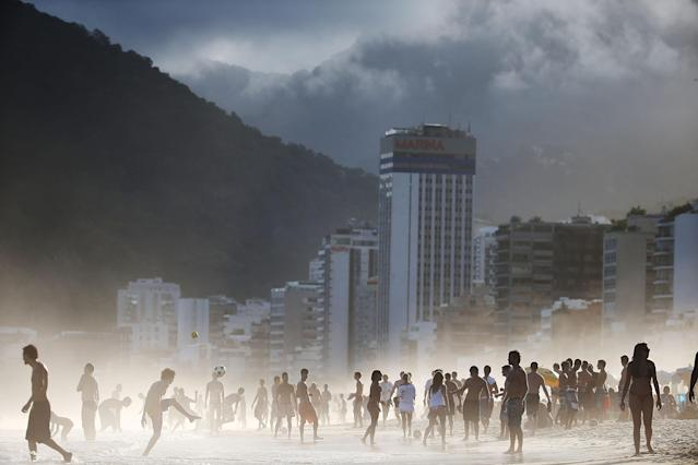 "RIO DE JANEIRO, BRAZIL - APRIL 21: Brazilians play altinha, a spin-off of soccer played on the beach, as others gather on Ipanema Beach in a low-lying mist on April 21, 2014 in Rio de Janeiro, Brazil. Altinha is Portuguese for ""a little higher"" and involves players attempting to keep the ball in the air without using their hands. Brazilians play many spin-offs of soccer including altinha, footvolley and futsal. Brazil is gearing up to host the 2014 FIFA World Cup in June. (Photo by Mario Tama/Getty Images)"