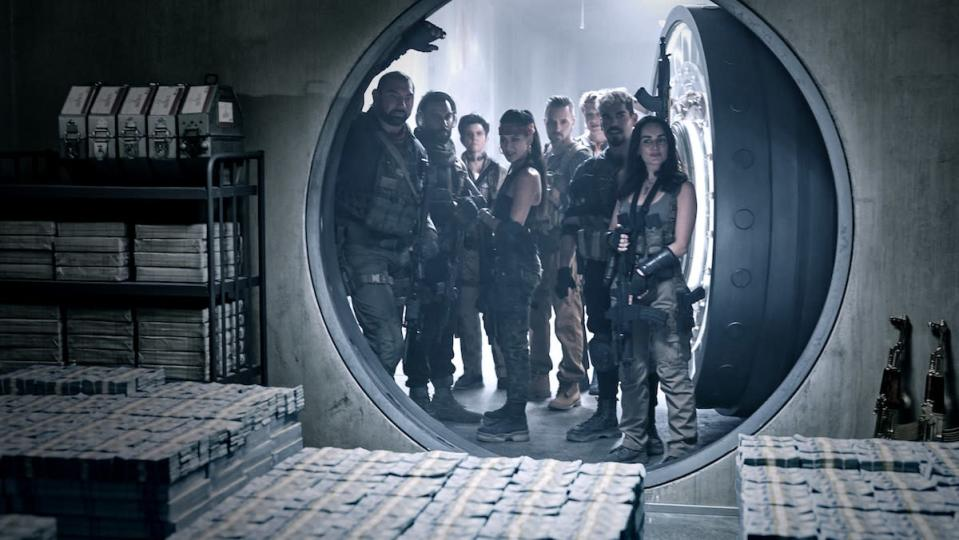 Armed mercenaries in fatigues stand in a round vault door looking at piles of money in Zack Snyder's Army of the Dead