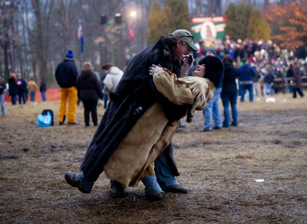 PUNXSUTAWNEY, PA - FEBRUARY 2: Treg Wentling and Shirley Wentling of Derry, PA dance in celebration after Punxsutawney Phil came from his den at the 126th annual Groundhog Day festivities on February 2, 2012 in Punxsutawney, Pennsylvania. The groundhog saw his shadow, revealing that there would be 6 more weeks of winter. Groundhog Day is a popular tradition in the United States and Canada. A smaller than usual crowd this year of less than 18,000 people spent a night of revelry awaiting the sunrise and the groundhog's exit from his winter den. If Punxsutawney Phil sees his shadow he regards it as an omen of six more weeks of bad weather and returns to his den. Early spring arrives if he does not see his shadow causing Phil to remain above ground. (Photo by Jeff Swensen/Getty Images)