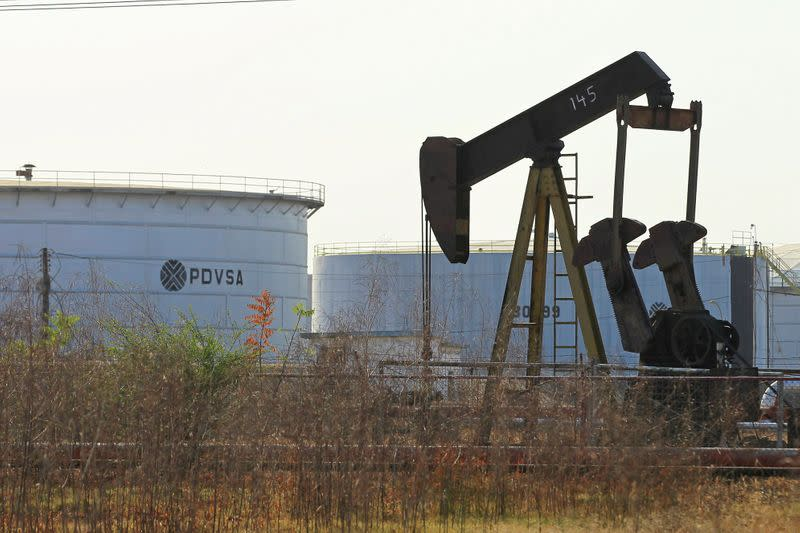 FILE PHOTO: An oil pumpjack and a tank with the corporate logo of state oil company PDVSA are seen in an oil facility in Lagunillas