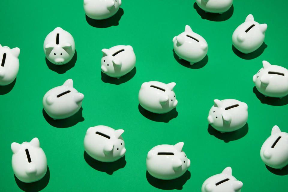 16 small white piggy banks placed randomly on green surface, high angle of view