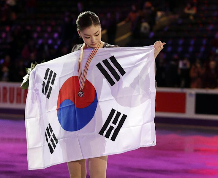 Kim Yu-na of South Korea holds the flag after winning the the gold medal in the ladies competition at the World Figure Skating Championships Saturday, March 16, 2013, in London, Ontario. (AP Photo/Darron Cummings)
