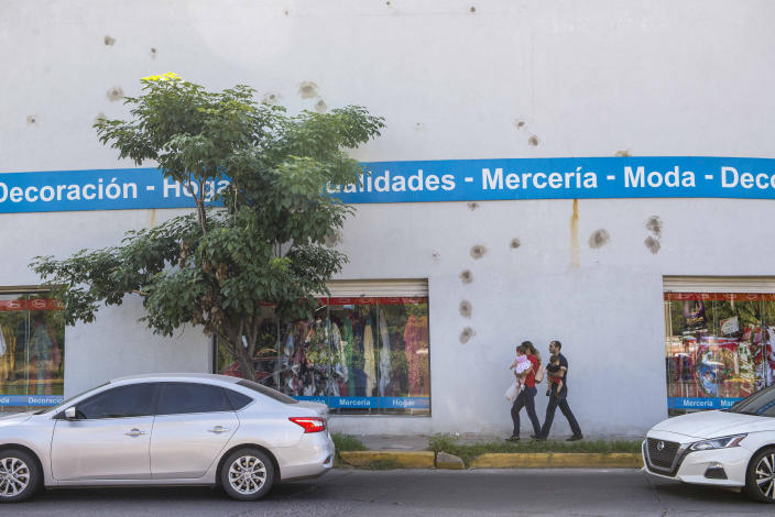 """Bullet holes cover the wall of a home decor store after a recent shootout in Culiacan, Mexico, Saturday, Oct. 26, 2019. The physical scars of the Oct. 17 gunbattles _ what's come to be known as """"black Thursday"""" by residents of Culiacan, the capital of Sinaloa and a stronghold of the Sinaloa cartel long led by Joaquín """"El Chapo"""" Guzmán _ are beginning to heal, but residents are still coming to grips with the worst cartel violence in recent memory. (AP Photo/Augusto Zurita)"""